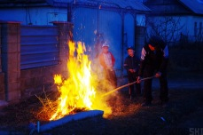 Karakol, Kyrgyzstan. A father and sons burn some branches after having cleaned up their garden. The kids look into the flames in delight.
