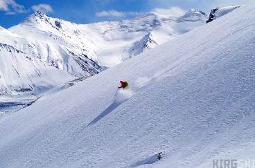 Glacier sans nom 2, sud-ouest de Kara-Say Nord, Ak-Shirak, Kirghizstan. C'est le moment de profiter de la descente, avec une neige encore legère. Au fond les sommets qui bordent la vallée de Kara-Say, d'environ 4500 m d'altitude.