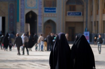"Two women just outside the holy Shrine, dressed in the black ""chador"" robe."