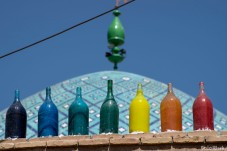 5 coloured bottles sitting on the wall....