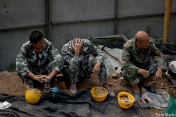 Several workers in military surplus rest from the heat
