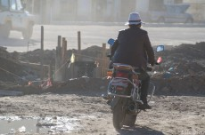 Motorbikes and cars kick up dust and grime