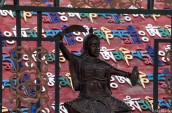 A statue with lines of tibetan script behing, decorating the huge (and new) temple in Madoi