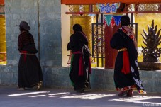 Worshipers head to the temple, strocking the prayer wheels